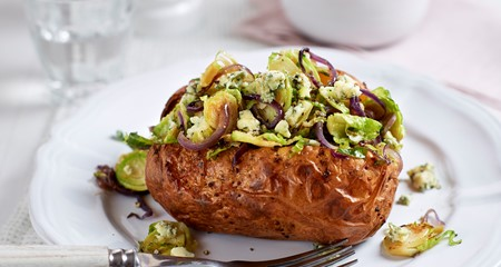 A cooked jacket potato on a plate topped with Brussel sprouts, crumbled blue cheese and red onion